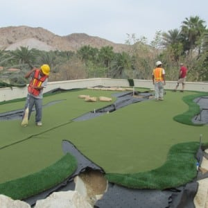 three men installing and sweeping rooftop putting green