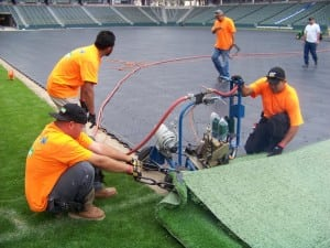 field installers working with the industrial carpet binder during turf installation