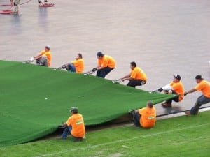 group of field installers stretch and spread out artificial football field turf on base panels