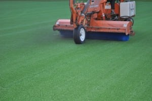 tractor sweeping artificial football field turf