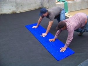 two men flattening fabric with sport court tiles in backyard basketball installation