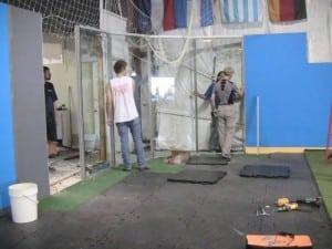 men installing plexiglass wall panels around indoor artificial turf field