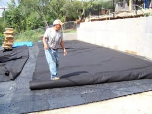 man rolling out fabric on top of base panels for backyard basketball court installation