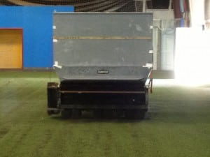 tractor applying rubber infill onto indoor artificial turf soccer field