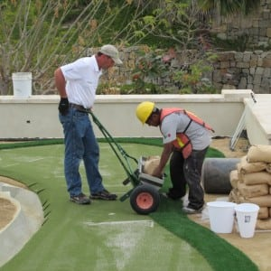 installer adds more sand to infill applicator