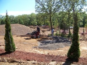 installers creating level area on construction site for artificial turf
