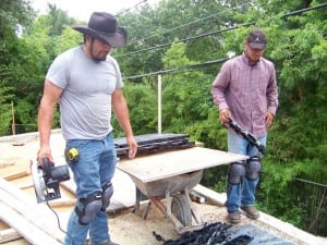 two men cutting base panels for backyard court installation
