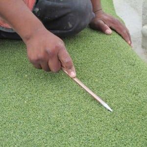 installer measuring putting green turf